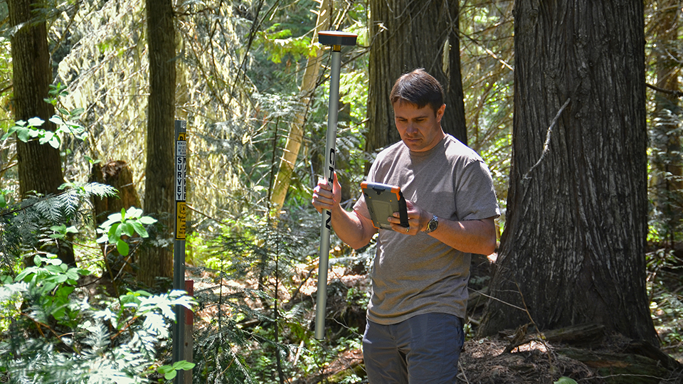 Man in forest using Mesa and Geode to map the location of natural resources using the Uinta software